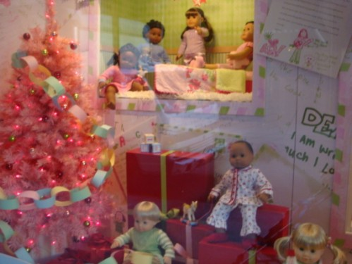 American Girl dolls in window display with pink Christmas tree
